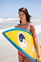 Woman holding a surfboard on the beach