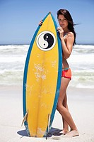 Portrait of a woman standing on the beach with surfboard