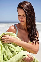 Woman wiping her body with towel on beach