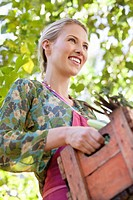 Smiling woman holding a crate of vegetables