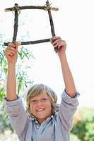 Portrait of a cute little boy holding frame of driftwood with arms raised outdoors