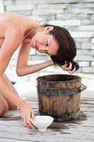 Woman washing hair into a bucket (thumbnail)