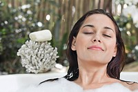 Beautiful young woman taking bubble bath with her eyes closed