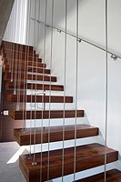 Wooden staircase with white walls and metal railing