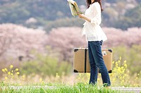 Woman walking with suitcase and map