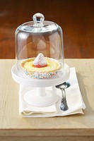 Lemon and strawberry tartlet under a glass dome