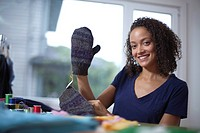 Attractive young woman showing glove that she has sewn