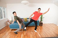 Two young men reaching while playing motion sensor video game