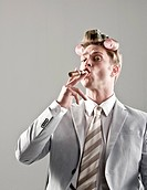 portrait of businessman with curlers in hair and smoking cigar