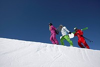 group of three people with skis and snowboards walking up mountain