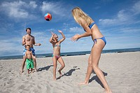 young family playing with ball on the beach