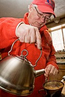 Man 62 pouring water from tea kettle to make coffee  Cable Wisconsin WI USA