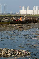 Children on boat in rubbish filled water, with city skyscrapers in background, Muara Karang, Jakarta, Java, Indonesia