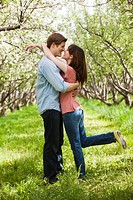 USA, Utah, Provo, Young couple embracing in orchard