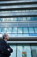 Executive looking at office building in thought