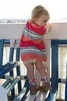 Toddler girl standing on chair, peeking over balcony railing, rear view