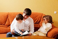 Dad reading book to daughters