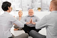 Businesspeople exercising yoga in office