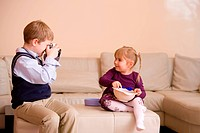 Boy taking picture of his sister