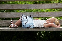 A one-year-old caucasian girl lying on a bench