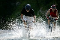 Two young men guiding their mountainbikes through a rivulet, blurred motion
