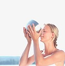 Young Woman drinking from Metal Bowl _ Wellness