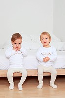 Two toddlers sitting side by side on bed, Berlin, Germany
