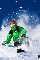 A skier skis hard through the exploding powder snow