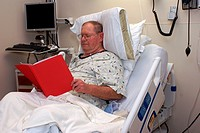 Hospital patient in bed reading information