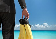 Businessman carrying fins on beach