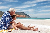 Older man with grandson on beach
