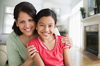 Hispanic mother hugging daughter in living room
