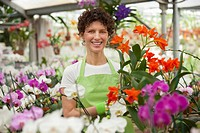 Hispanic woman tending flowers in plant nursery