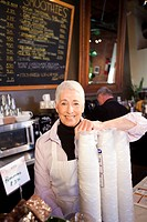 Caucasian business owner standing with disposable cups in cafe