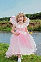 Girl wearing fairy costume by creek