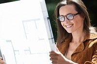 Woman reading blueprints outdoors