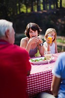 Woman eating with family at picnic table