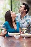 Playful couple eating together at table