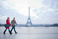 Couple walking past the Eiffel Tower