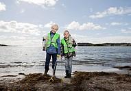 Children in safety vests cleaning beach