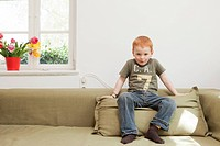 Boy sitting on sofa cushion
