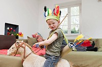 Boy in war bonnet playing with toys