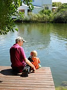 Man with grandson on jetty over lake