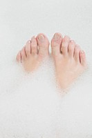 Woman's feet in bubble bath
