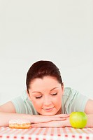 Charming woman posing with a donut and a green apple in the kitchen