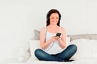 Pretty female relaxing with her mp3 while sitting on her bed