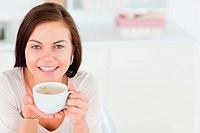 Smiling dark_haired woman having a coffee in her kitchen