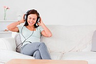 Smiling brunette listening to music in her living room