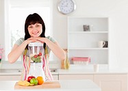 Attractive brunette woman posing with a mixer while standing in the kitchen
