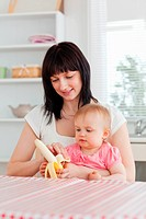 Beautiful brunette woman pealing a banana while holding her baby on her knees in the kitchen